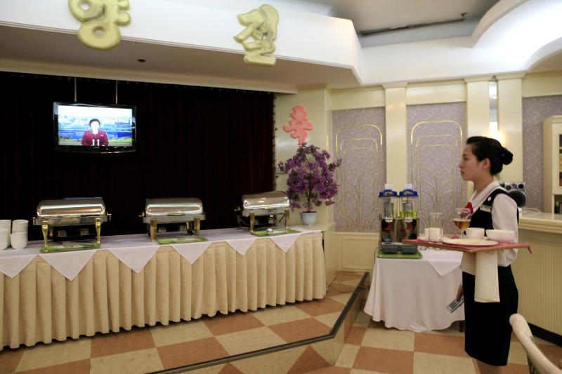 A North Korean waitress watches a North Korean TV news program acknowledging the country's failed rocket launch at a hotel restaurant in Pyongyang, North Korea, Friday, April 13, 2012. The much-anticipated rocket launch ended quickly in failure early Friday, splintering into pieces over the Yellow Sea soon after takeoff. (AP Photo/Ng Han Guan)