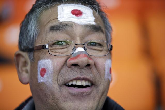 A Japanese skating fan, face painted with colors of his national flag, waits for the start of the men's 1000-meter speedskating race at the Adler Arena Skating Center at the 2014 Winter Olympics, Wednesday, Feb. 12, 2014, in Sochi, Russia. (AP Photo/David J. Phillip )