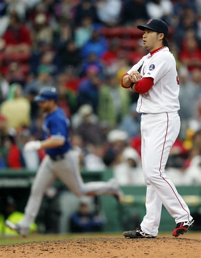 Boston Red Sox's Junichi Tazawa stands on the mound after giving up a solo home run to Toronto Blue Jays' Adam Lind, left, in the ninth inning of a baseball game in Boston, Saturday, May 11, 2013. The Blue Jays won 3-2. (AP Photo/Michael Dwyer)