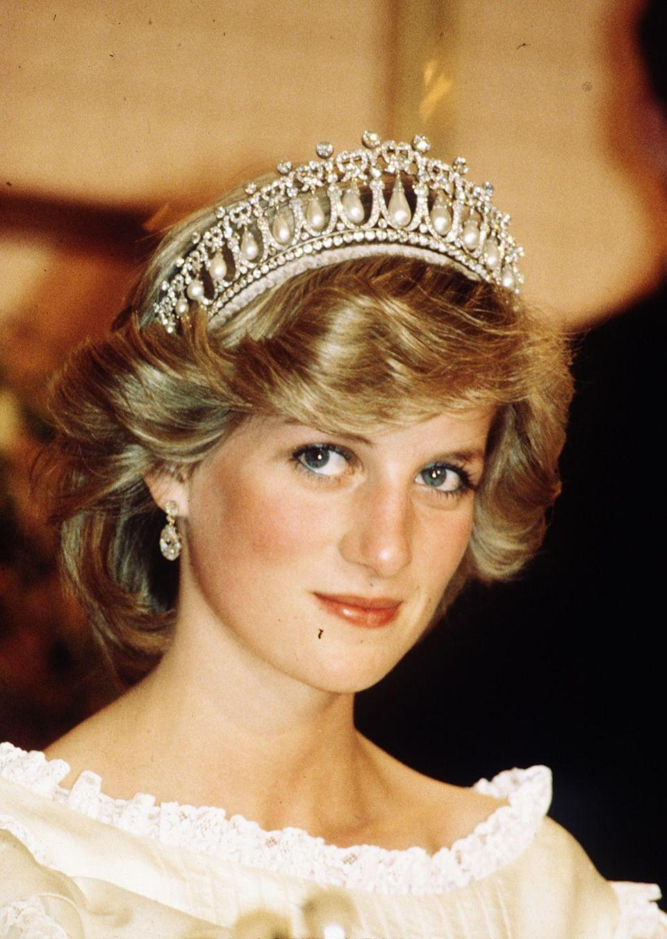 """<p>While visiting New Zealand, Diana chose to wear the famed Cambridge <a href=""""https://www.townandcountrymag.com/society/tradition/a10302981/cambridge-love-knot-tiara/"""" rel=""""nofollow noopener"""" target=""""_blank"""" data-ylk=""""slk:Lover's Knot"""" class=""""link rapid-noclick-resp"""">Lover's Knot</a> tiara. The headpiece dates back to Queen Mary, who commissioned the tiara from jewelry house Garrard in 1914. The tiara was then passed down to Queen Elizabeth II, who then lent it to Diana. Now, the Duchess of Cambridge is often spotted in the intricate, beautiful headpiece. </p>"""