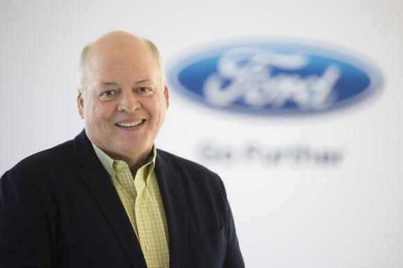Hackett is seated before a white backdrop with a Ford logo.