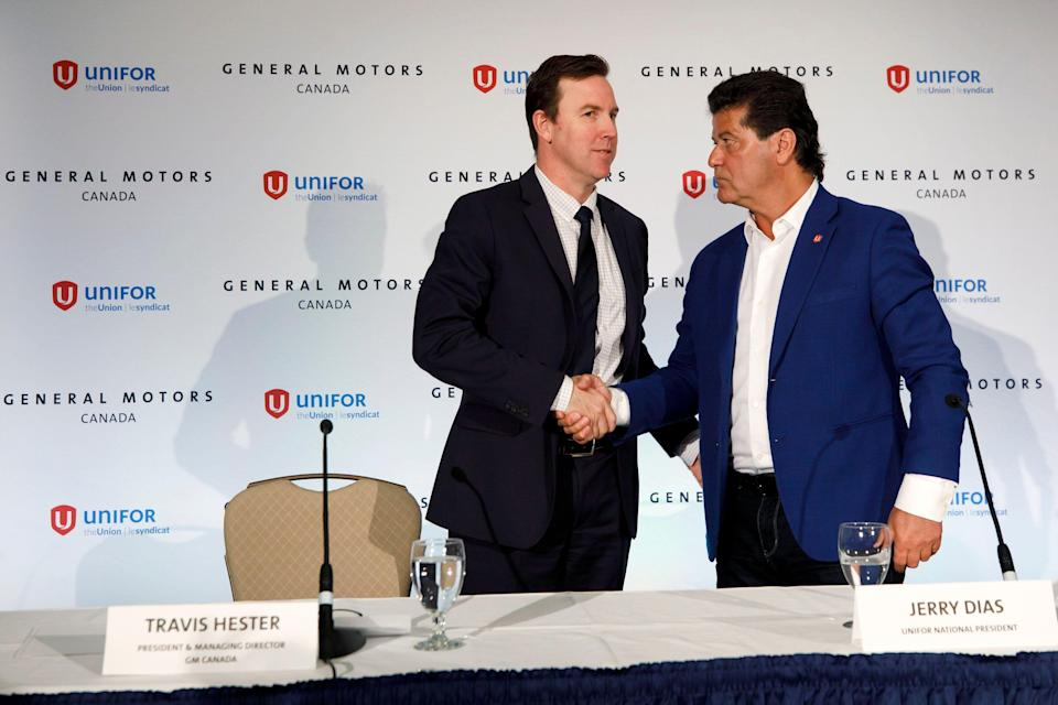 General Motors Canada president Travis Hester, left, and Unifor union national president Jerry Dias shake hands during a press conference, Wednesday, May 8, 2019, in Toronto, where GM announced they are investing in its Oshawa, Ontario, plant to transition the facility from manufacturing vehicles to stamping, sub-assembly and autonomous vehicle testing. (Cole Burston/The Canadian Press via AP)