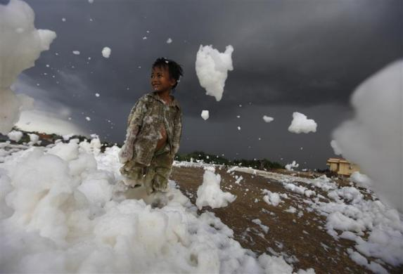 A child stands on foam from a polluted river at the Marunda flood canal in Jakarta December 14, 2011.