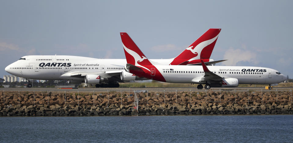 FILE - In this Aug. 20, 2015, file photo, two Qantas planes taxi on the runway at Sydney Airport in Sydney. Qantas Airways chief executive Alan Joyce said on Thursday, Feb. 25, 2021, he doesn't expect his airline will resume international travel except for New Zealand until late October, after the Australian population is vaccinated for COVID-19. (AP Photo/Rick Rycroft, File)