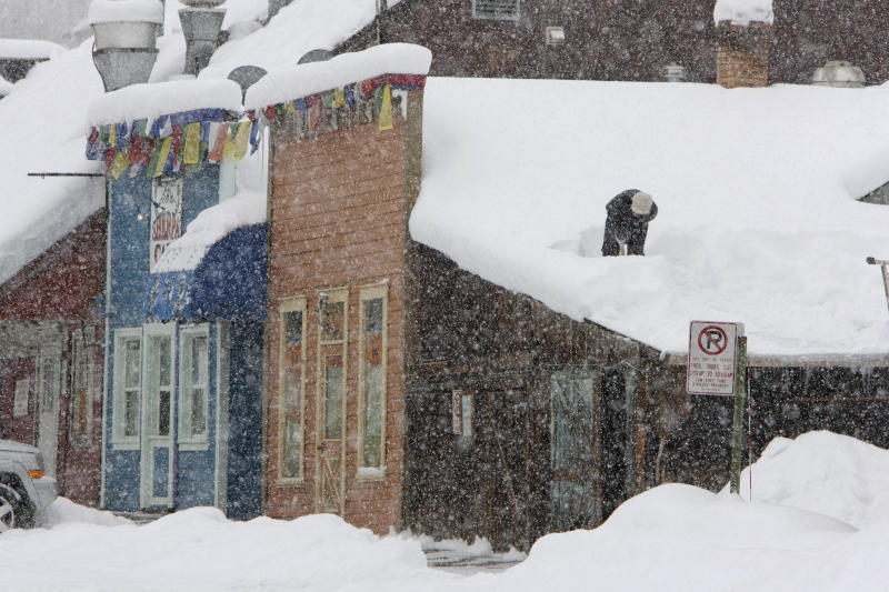 A person stands on top of a snow-covered roof in Crested, Butte, Colo. on Saturday, Dec. 18, 2010 to remove it before the next serge of snow that is expected. A winter weather message was announced Saturday morning from the National Weather Service for West and Southwest mountains of Western Colorado and Eastern Utah. This warning is in effect until midnight Tuesday. (AP Photo/Nathan Bilow)