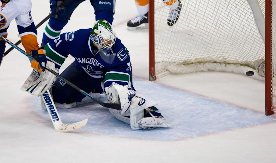 Vancouver Canucks' goalie Eddie Lack, of Sweden, allows a goal to New York Islanders' Matt Martin during third period NHL hockey action in Vancouver, British Columbia, on Monday March 10, 2014. (AP Photo/The Canadian Press, Darryl Dyck)