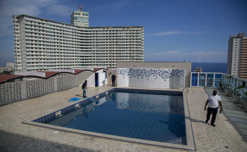 Workers do maintenance on the rooftop pool of the Capri Hotel during a lockdown affecting tourism to curb the spread of the COVID-19 pandemic in Havana, Cuba, Wednesday, June 17, 2020. Cuba's once-vibrant private hospitality sector, devastated by the three-month shutdown, remains closed to international business and will have to wait until later phases to try to begin to recover. (AP Photo/Ismael Francisco)