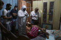 The body Raimundo Costa do Nascimento, 86, lies on a bed as the family mourns and a funeral worker in protection gear gets ready to pick up the body, amid the new coronavirus pandemic, at his home in Sao Jorge, Manaus, Brazil, Thursday, April 30, 2020. According to the family, Costa do Nascimento died of pneumonia and had to wait 10 hours for funerary services to come pick up his body. (AP Photo/Edmar Barros)