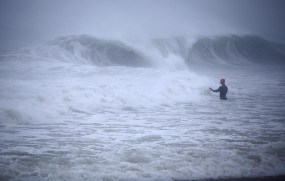Matt Prue, from Stonington, Conn., walks out into the Atlantic Ocean to body surf the waves from Tropical Storm Henri as it approaches Westerly, R.I., Sunday, Aug. 22, 2021. (AP Photo/Stew Milne)