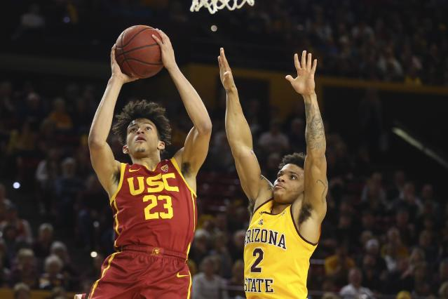 Southern California forward Max Agbonkpolo (23) scores against Arizona State guard Rob Edwards (2) during the first half of an NCAA college basketball game Saturday, Feb. 8, 2020, in Tempe, Ariz. (AP Photo/Ross D. Franklin)