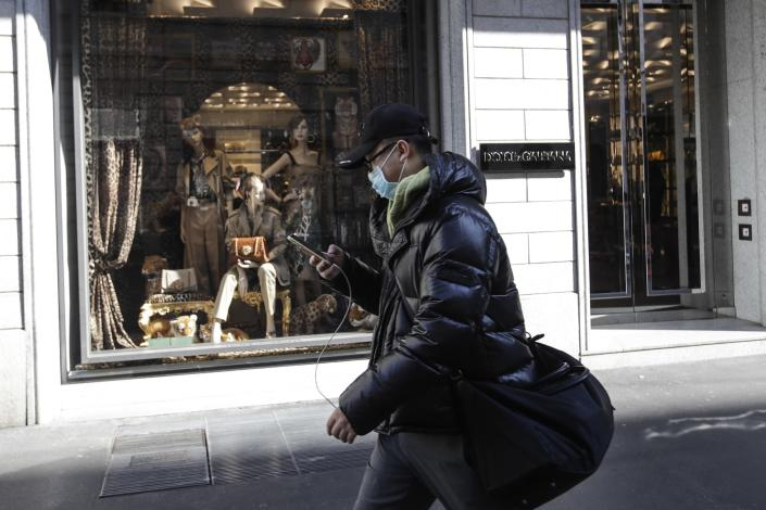A man wearing a mask checks his smartphone as he walks along Milan fashion district, Italy, Monday, Feb. 24, 2020. Police manned checkpoints around quarantined towns in Italy's north on Monday as authorities sought to contain cases of COVID-19 virus that have made Italy the focal point of the outbreak in Europe and fears of its cross-border spread. At least 190 people in Italy's north have tested positive for the virus and four people have died, including an 84-year-old man who died overnight in Bergamo, the Lombardy regional government reported. (AP Photo/Luca Bruno)