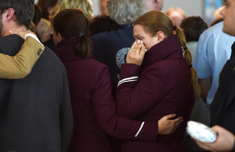 Employees of the German airline Lufthansa and subsidiary Germanwings mourn the victims of the Germanwings plane crash at Duesseldorf airport on March 26, 2015 (AFP Photo/Patrik Stollarz)