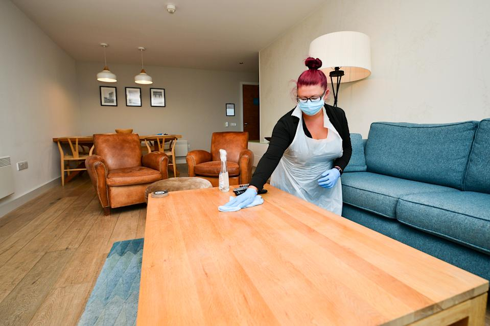 Head housekeeper Carolanne Rowe wears PPE as she deep cleans a hotel suite at St. Moritz Hotel and Spa, Cornwall, during room sanitizing in preparation ahead of reopening to guests. (Photo by Ben Birchall/PA Images via Getty Images)