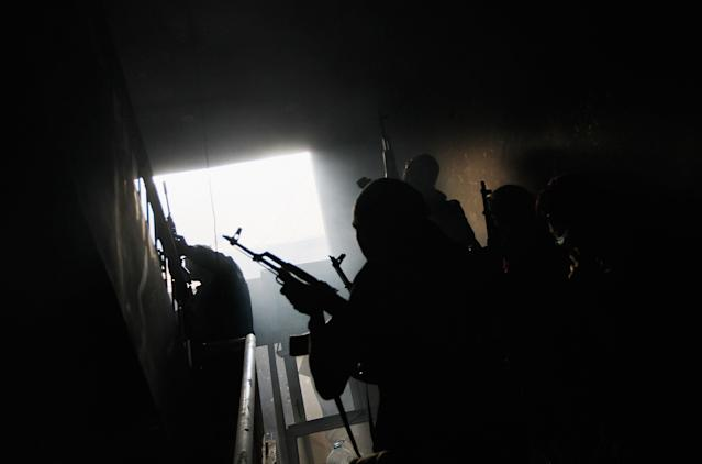 <p>Rebel fighters carefully move up a stairway in a building where they had trapped government loyalist troops during street fighting on Tripoli Street in downtown Misrata April 20, 2011 in Misrata, Libya. (Photo by Chris Hondros/Getty Images) </p>