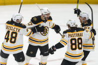 Boston Bruins center Patrice Bergeron (37) celebrates his goal with defenseman Matt Grzelcyk (48), right wing David Pastrnak (88) and center Brad Marchand (63) during the first period of Game 2 of an NHL hockey Stanley Cup first-round playoff series against the Washington Capitals Monday, May 17, 2021, in Washington. (AP Photo/Alex Brandon)