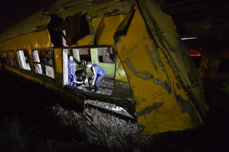 People inspect at the wreckage of a train in the Giza in Badrashin, about 40 km west of Cairo, on January 15, 2013, at least 19 people where killed and injured 105. The train carrying conscripts from south Egypt to Cairo derailed in the Giza neighbourhood of Badrasheen, state media reported. Giza governor Ali Abdelrahman said emergency services were at the scene and ambulances were ferrying the injured to hospital. The accident is the latest in a string of transport disasters plaguing the country. AFP PHOTO / KHALED DESOUKI