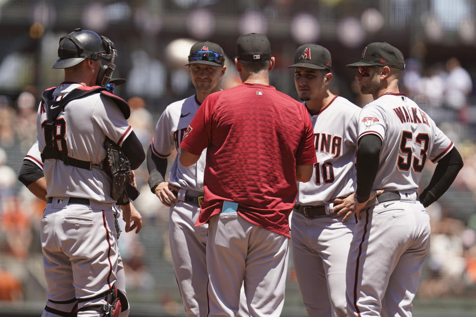 Arizona Diamondbacks manager Torey Lovullo, front center, talks with from left to right, Carson Kelly, Nick Ahmed, Josh Rojas and Christian Walker during a pitching change in the third inning of a baseball game against the San Francisco Giants, Thursday, June 17, 2021, in San Francisco. (AP Photo/Eric Risberg)