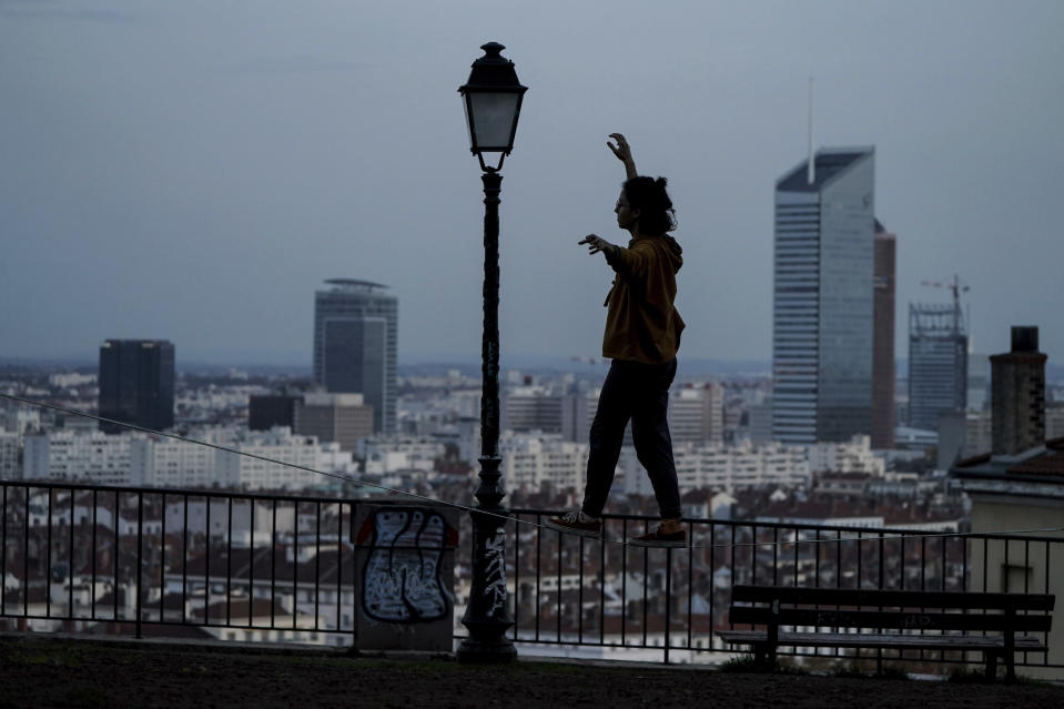A woman balances on a slackline on a hill above Lyon, central France, Friday, Nov. 6, 2020. In France, which is in a monthlong partial lockdown to stop fast-rising virus hospitalizations and deaths, restaurants and non-essential stores are closed for a month, but schools remain open and there are several other exceptions to the lockdown. (AP Photo/Laurent Cipriani)