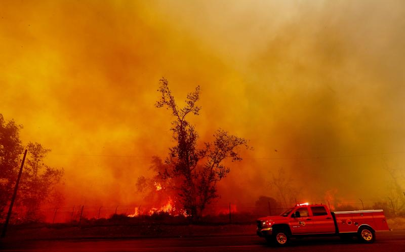 Thick smoke billows along Foothill Boulevard as the Creek Fire burns heavy brush in Los Angeles' Sylmar neighborhood on Dec. 5, 2017.