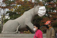 People wearing face masks to help protect against the spread of the coronavirus pass by a statue with a face mask at a park in Seoul, South Korea, Friday, Oct. 16, 2020. South Korea's daily coronavirus tally has dropped below 50 for the first time in more than two weeks despite reports of small-scale local infections. (AP Photo/Ahn Young-joon)