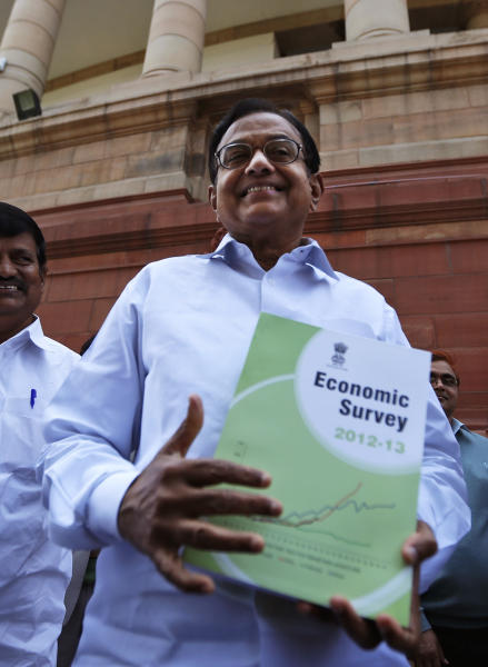 Indian Finance Minister Palaniappan Chidambaram comes out of the Indian Parliament with a copy of the economic survey in New Delhi, India, Wednesday, Feb. 27, 2013. Chidambaram is scheduled to present the annual budget for the next fiscal year in the Parliament on Thursday Feb. 28. (AP Photo/ Saurabh Das)