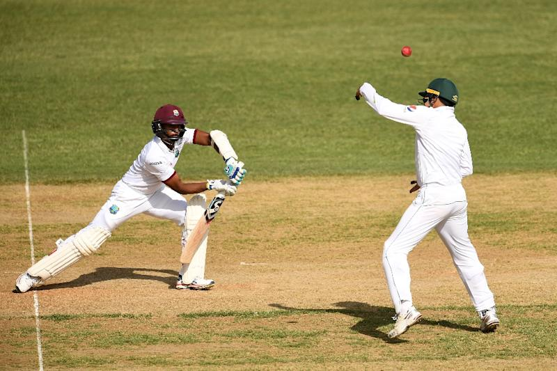 West Indies' batsman Shane Dowrich (L) plays a shot as Pakistan's Azhar Ali tries to stop on day one of the first Test match between West Indies and Pakistan at the Sabina Park in Kingston, Jamaica, on April 21, 2017 (AFP Photo/Jewel SAMAD)