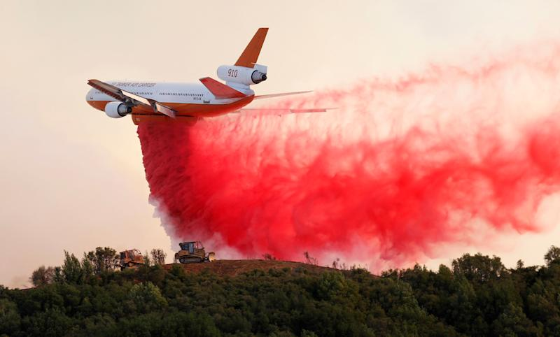 A DC-10 air tanker drops fire retardant along the crest of a hill to protect the two bulldozers below that were cutting fire lines near the River fire on Thursday. (Fred Greaves / Reuters)