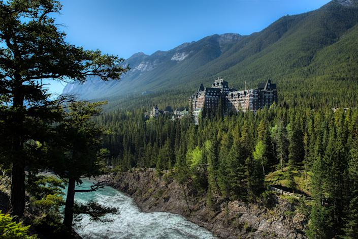 Stunning view of the iconic Fairmont Banff Springs Hotel situated near the bottom of Sulphur Mountain with Bow Falls below, Banff National Park, Alberta, Canada
