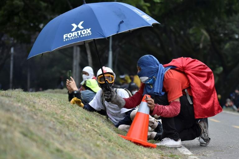 Anti-government demonstrators take cover during clashes with police in Cali, Colombia, on May 28, 2021