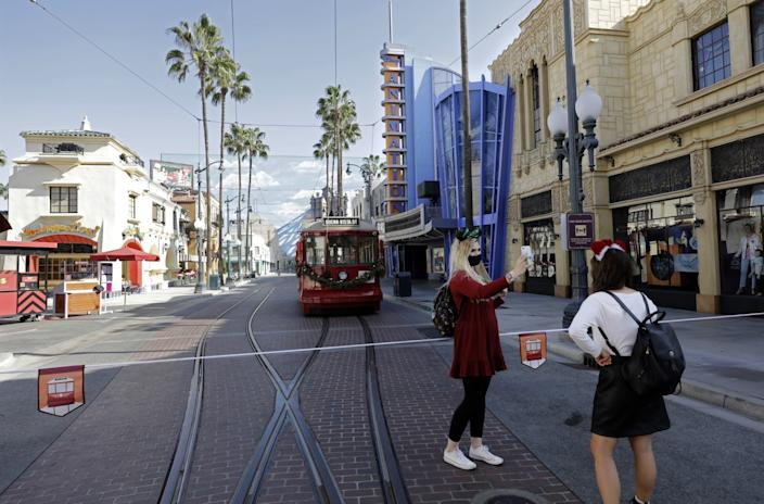 Two pedestrians and a bus on Buena Vista Street.