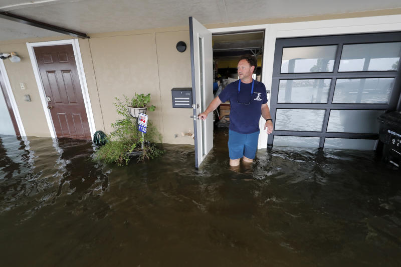 Rudy Horvath walks out of his home, a boathouse in the West End section of New Orleans, as it takes on water a from storm surge in Lake Pontchartrain in advance of Tropical Storm Cristobal, Sunday, June 7, 2020. (AP Photo/Gerald Herbert)