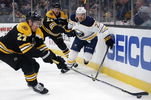 Buffalo Sabres' Sam Reinhart (23) battles for the puck with Boston Bruins' John Moore (27) and Brandon Carlo (25) during the first period of an NHL hockey game in Boston, Sunday, Dec. 16, 2018. (AP Photo/Michael Dwyer)