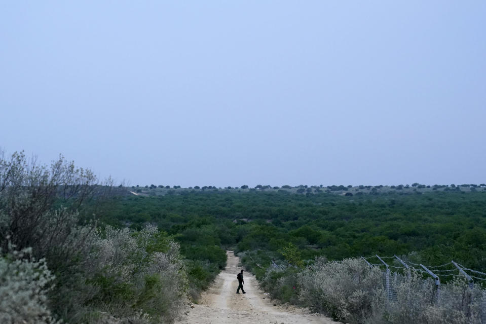 FILE - In this May 11, 2021, file photo a Border Patrol agent walks along a dirt road near the U.S.-Mexico border, in Roma, Texas. The Biden administration says families arriving at the U.S. border with Mexico will have their cases fast-tracked in immigration court, an announcement on Friday, May 28, that comes less than two weeks after said it was easing pandemic-related restrictions on seeking asylum. Under the plan, immigration judges in 10 cities will aim to decide cases within 300 days. (AP Photo/Gregory Bull)