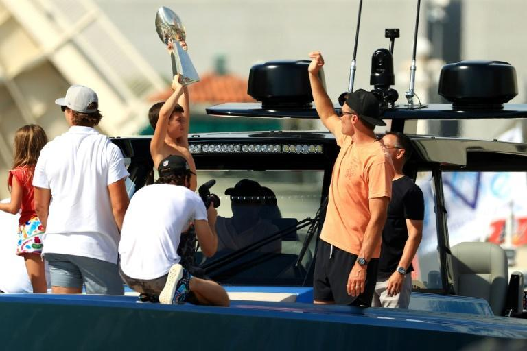 Tampa Bay Buccaneers star quarterback Tom Brady, waving at right on the back of his yacht, would eventually throw the Super Bowl trophy, top center, onto the trailing boat of teammate Rob Gronkowski during a river parade Wednesday to celebrate their NFL title