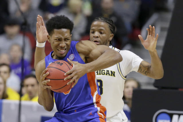 <p>Florida's KeVaughn Allen (5) is guarded by Michigan's Zavier Simpson, right, during the first half of a second round men's college basketball game in the NCAA Tournament, in Des Moines, Iowa, Saturday, March 23, 2019. (AP Photo/Nati Harnik) </p>