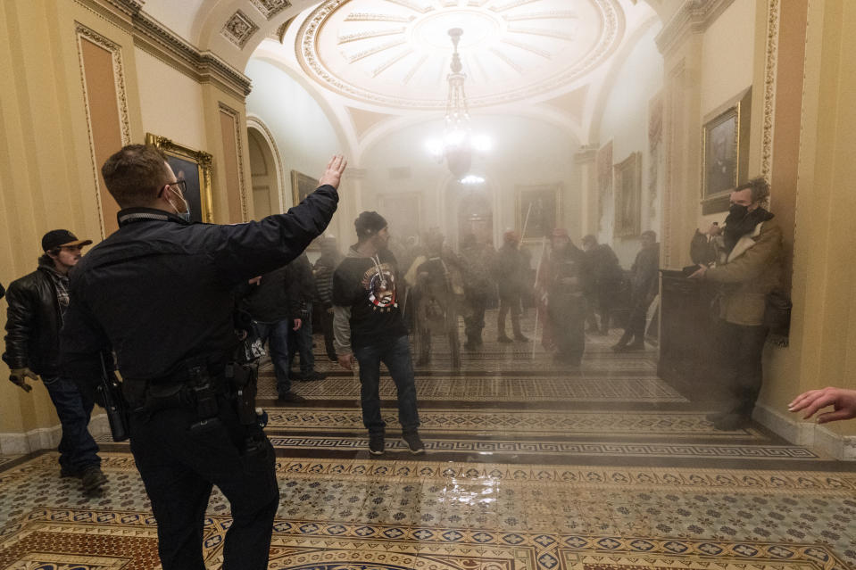 FILE - In this Jan. 6, 2021 file photo smoke fills the walkway outside the Senate Chamber as insurrectionists loyal to President Donald Trump are confronted by U.S. Capitol Police officers inside the Capitol in Washington. Arguments begin Tuesday, Feb. 9, in the impeachment trial of Donald Trump on allegations that he incited the violent mob that stormed the U.S. Capitol on Jan. 6. (AP Photo/Manuel Balce Ceneta, File)