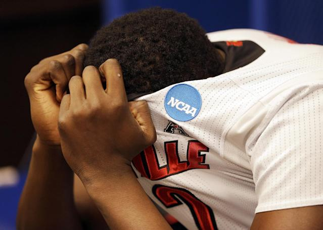 10ThingstoSeeSports - Louisville's Akoy Agau covers his head in the locker room after an NCAA Midwest Regional semifinal college basketball tournament game against Kentucky, Saturday, March 29, 2014, in Indianapolis. Kentucky won 74-69. (AP Photo/David J. Phillip, File)