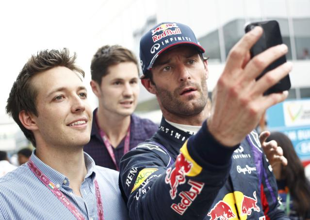Red Bull Formula One driver Mark Webber of Australia takes a photo of himself with a fan during the Indian F1 Grand Prix at the Buddh International Circuit in Greater Noida, on the outskirts of New Delhi, October 25, 2013. REUTERS/Anindito Mukherjee (INDIA - Tags: SPORT MOTORSPORT F1)