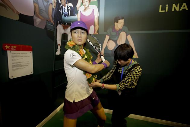 A woman puts a garland onto a wax figure of Chinese tennis player Li Na at the Madame Tussauds Museum in Wuhan in central China's Hubei province Saturday, Jan. 25, 2014. (AP Photo)