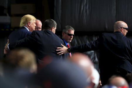 Secret Service agents surround U.S. Republican presidential candidate Donald Trump during a disturbance as he speaks at Dayton International Airport in Dayton, Ohio, March 12, 2016.  REUTERS/Aaron P. Bernstein
