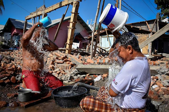 <p>Two men bathe near their homes damaged or destroyed by an earthquake in Kayangan District, Lombok, Indonesia, Aug. 10, 2018. (Photo: Antara Foto/Ahmad Subaid via Reuters) </p>
