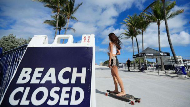 PHOTO: A skateboarder passes a 'Beach Closed' sign on the boardwalk on March 22, 2020 in Miami Beach, Florida. The city of Miami Beach has closed all parks and beaches due to COVID-19, however the boardwalk is open for people to exercise. (Cliff Hawkins/Getty Images)