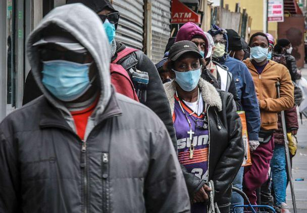 PHOTO: People wait for a distribution of masks and food from the Rev. Al Sharpton in the Harlem neighborhood of New York, April 18, 2020, after a new state mandate was issued requiring residents to wear face coverings in public due to COVID-19. (Bebeto Matthews/AP)