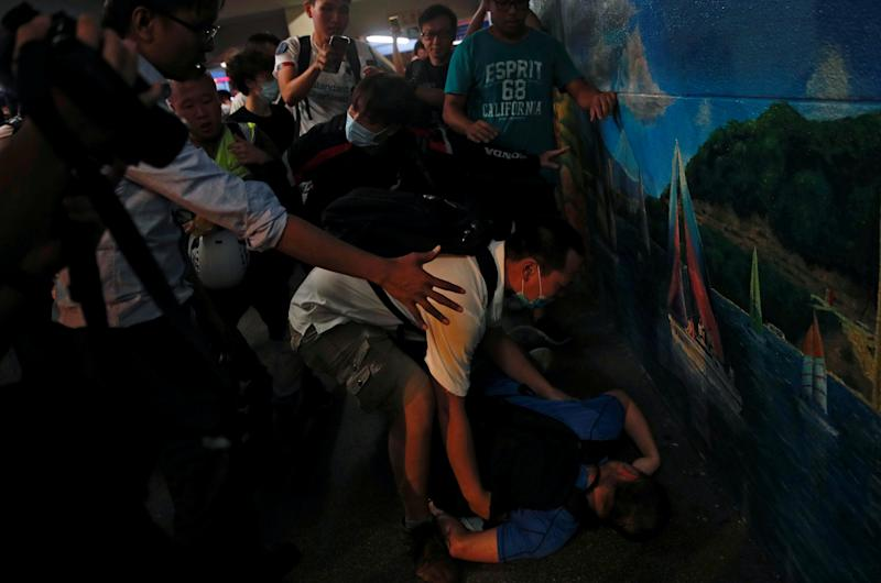 A pro-government supporter passes out after he was beaten up by anti-extradition supporters outside the office of pro-China lawmaker Junius Ho in Tsuen Wan in Hong Kong, China July 22, 2019. (Photo: Edgar Su/Reuters)
