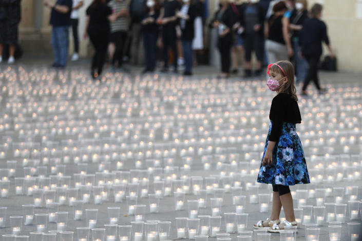 A young girl walks to light up candles to commemorate victims of the COVD-19 pandemic at the Prague Castle in Prague, Czech Republic, Monday, May 10, 2021. The Czech Republic is massively relaxing its coronavirus restrictions as the hard-hit nation pays respect to nearly 30,000 dead. (AP Photo/Petr David Josek)