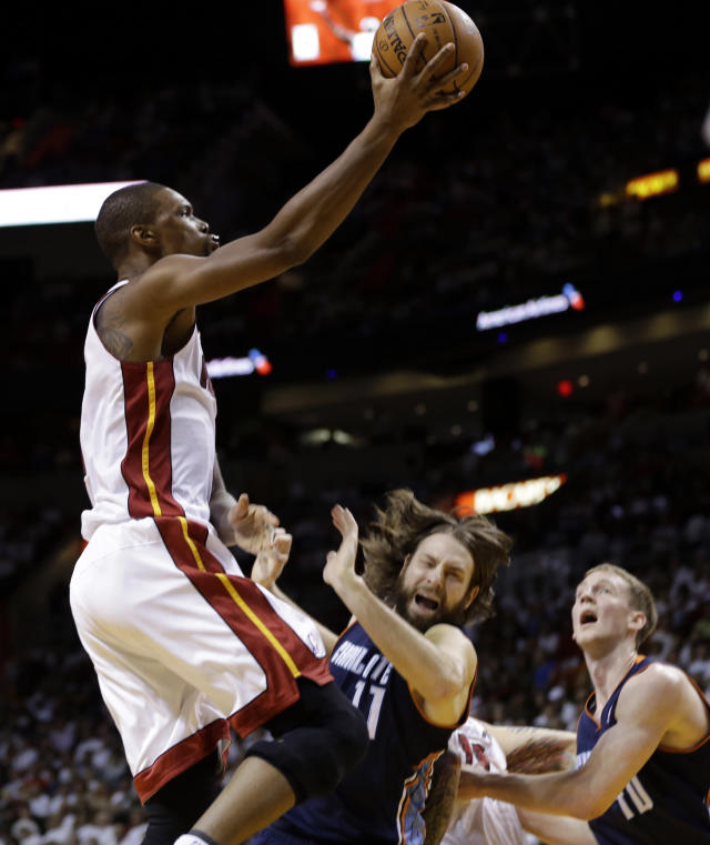 Miami Heat's Chris Bosh, left, shoots over Charlotte Bobcats' Josh McRoberts (11) during the first half in Game 2 of an opening-round NBA basketball playoff series, Wednesday, April 23, 2014, in Miami. (AP Photo/Lynne Sladky)