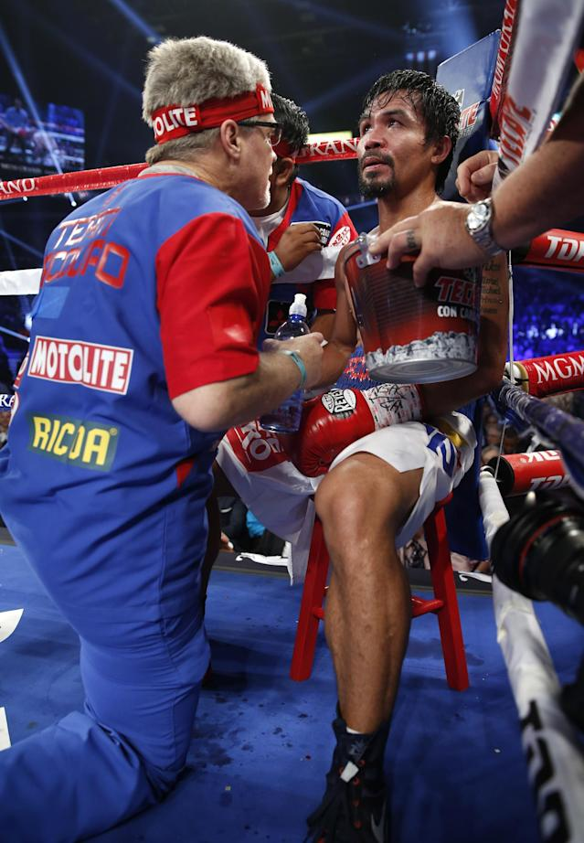 Manny Pacquiao, right of the Philippines, talks with trainer Freddie Roach during a WBO welterweight title boxing fight against Timothy Bradley on Saturday, April 12, 2014, in Las Vegas. (AP Photo/Eric Jamison)