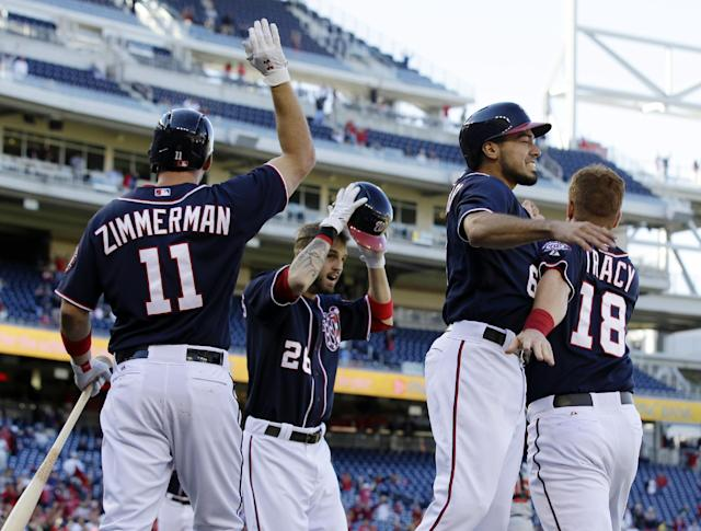 Washington Nationals' Ryan Zimmerman (11), Jeff Kobernus (26), Anthony Rendon (6) and Chad Tracy (18), celebrate after Kobernus and Rendon scored to win the game in the ninth inning of the first baseball game of a doubleheader against the Atlanta Braves at Nationals Park Tuesday, Sept. 17, 2013, in Washington. The Nationals won 6-5. (AP Photo/Alex Brandon)