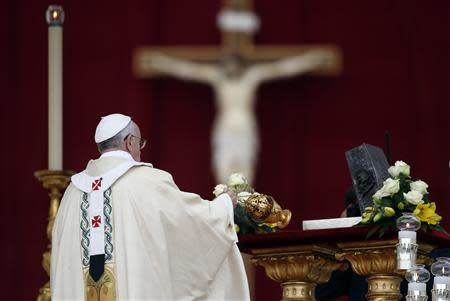Pope Francis blesses the relics of the Apostle Peter on the altar during a mass at St. Peter's Square at the Vatican November 24, 2013. REUTERS/Stefano Rellandini