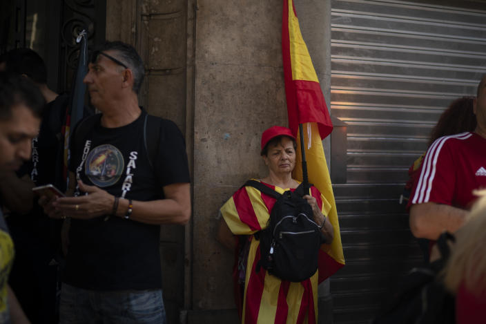 A woman holding a Spanish flag stands on the sidewalk as members of National Police and Guardia Civil protest demanding better pay in Barcelona, Spain, Saturday, Sept. 29, 2018. (AP Photo/Felipe Dana)